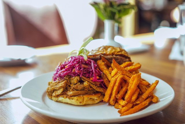 Criollo Restaurant's Hot Pulled Pork Sandwich, dressed with marinated red cabbage and onions, toasted onion roll and horseradish caraway sauce