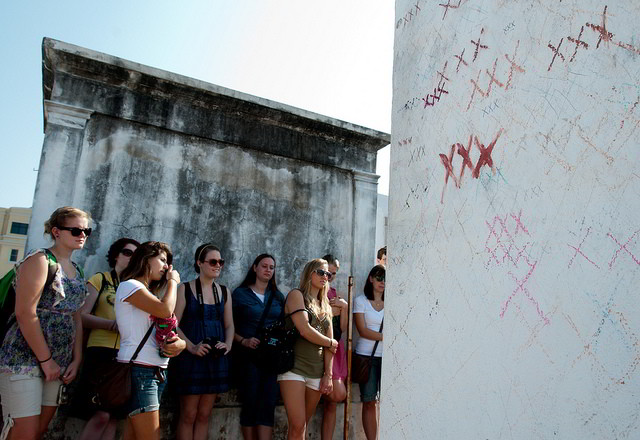 Students visit the grave of voodoo queen Marie Laveau in St. Louis Cemetery #1. (Photo via Tulane Public Relations on Flickr)
